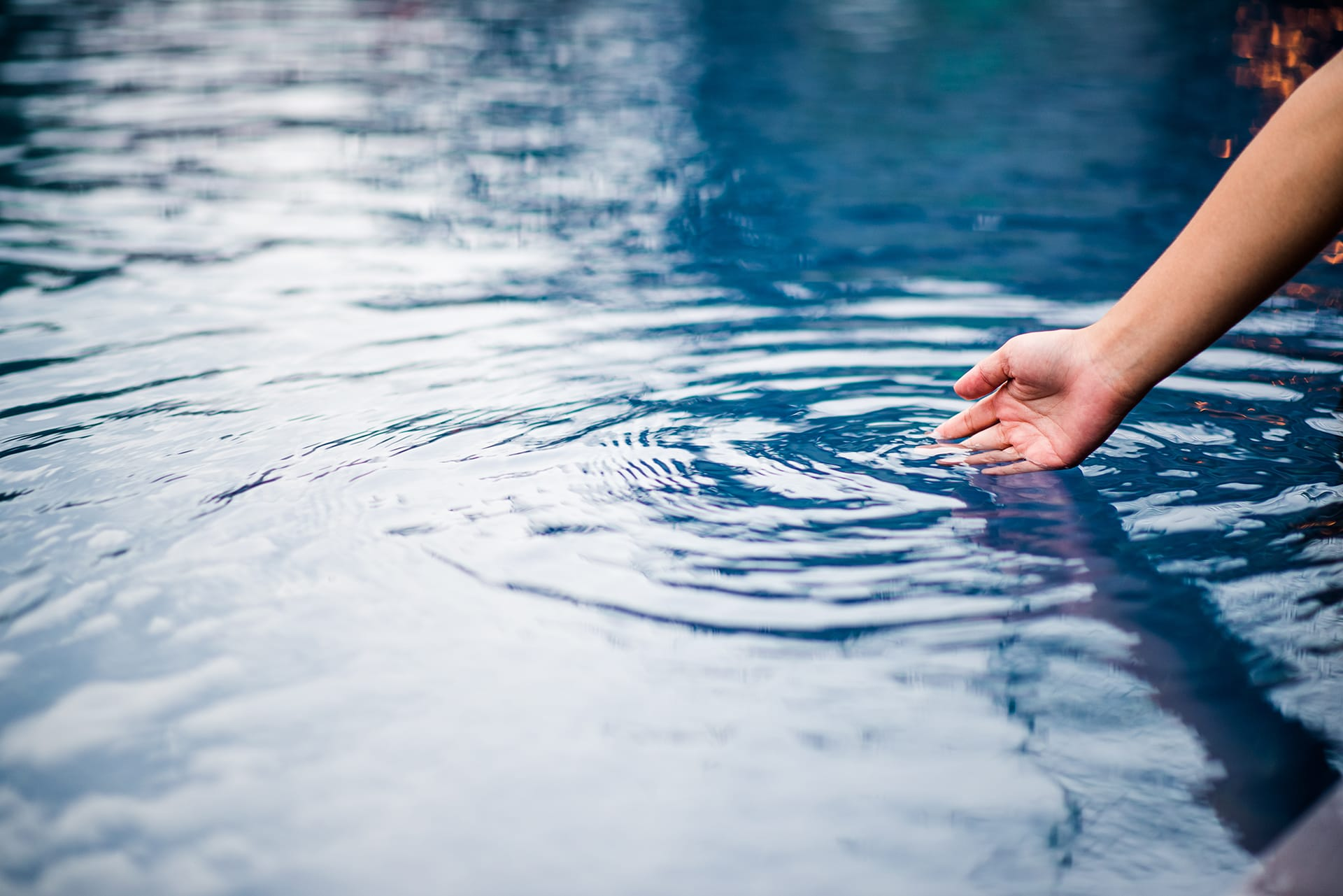 hand-that-touches-blue-water-pool-is-clean-bright-with-drop-water-o